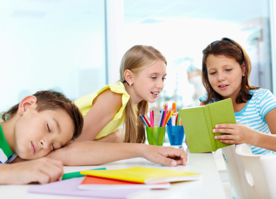 Cute schoolgirl showing her classmate her notes, tired boy napping on desk near by