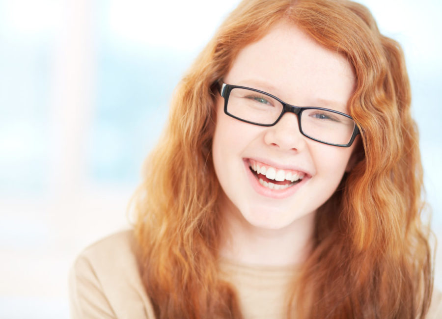 Teenage girl in eyeglasses looking at camera and laughing