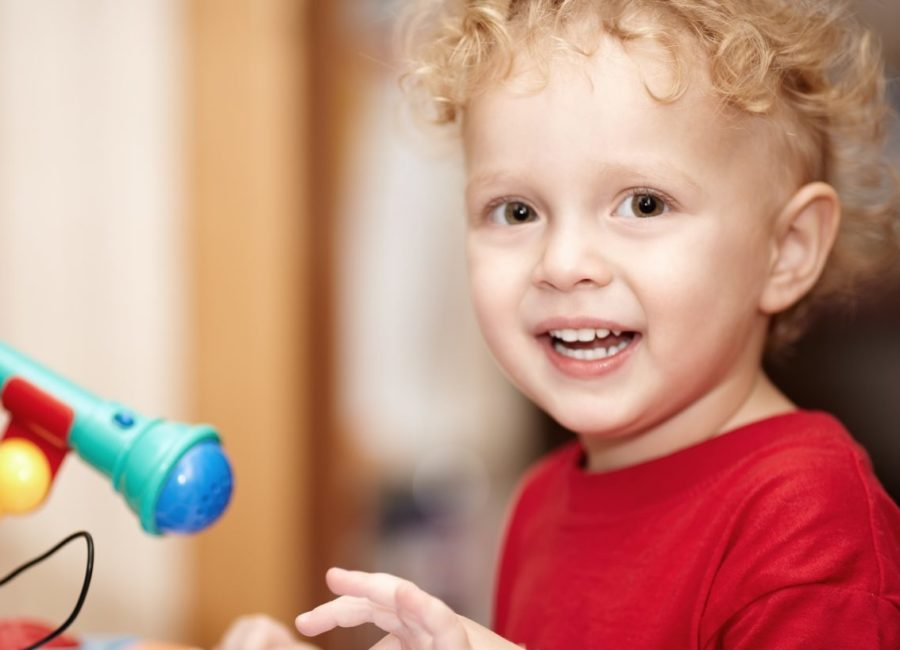 Adorable little boy with a mischievous smile and curly blond hair playing with a colourful plastic toy microphone
